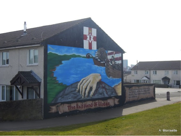 Shankill mural depicting the Red Hand of Ulster. According to legend, two kings agreed that the first man who touch this piece of land would own it. They raced toward the land in boats, neck and neck. In a desperate effort to claim the land, one king cut off his hand and threw it ashore. The Red Hand of Ulster (and the associated flag you can see at the top of the mural) has become a complicated symbol in Ireland. The legend predates English occupation (in the 1100s), but it has been adopted by Loyalists and Unionists.